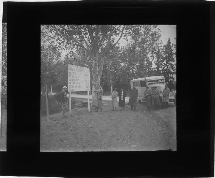 Groupe et véhicule de la Compagnie générale transsaharienne posant à côté d'un panneau de signalisation kilométrique indiquant Camp des Chênes, Médéa, Djelfa