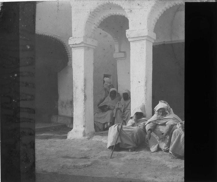 Hommes assis devant une maison à arcades