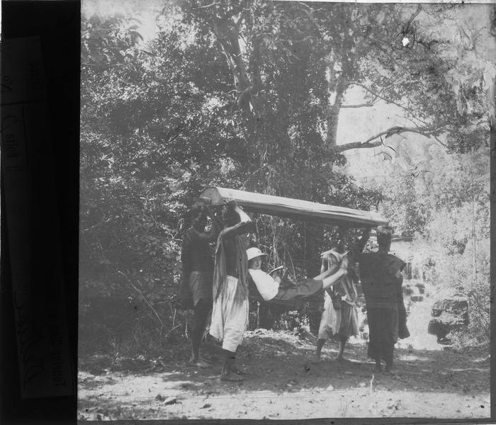 Femme en tenue coloniale portée dans un hamac par des autochtones