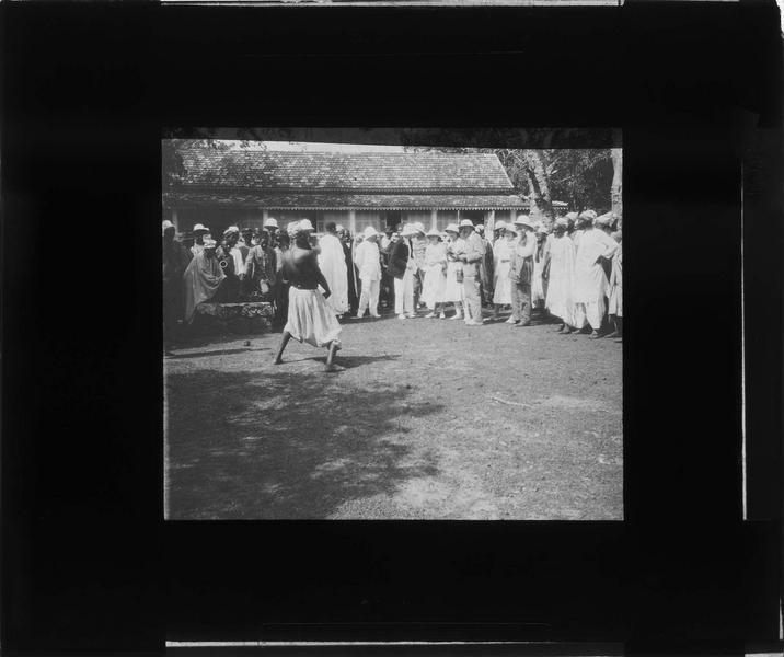 Musiciens et danseur devant un groupe en tenue coloniale
