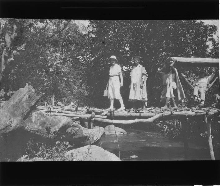 Groupe traversant une passerelle avec voyageur en tenue coloniale dans un hamac