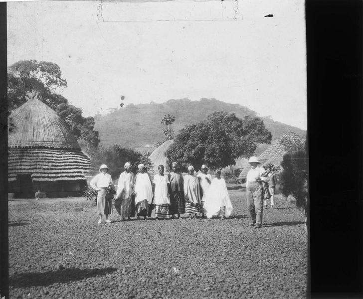 Autochtones et touristes en tenue coloniale dans un village