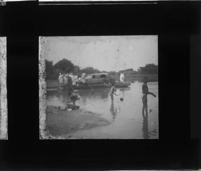 Autochtones sur les bords de la rivière Bani et voiture sur un bac en arrière-plan
