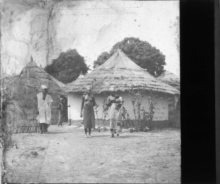 Autochtones posant devant des huttes