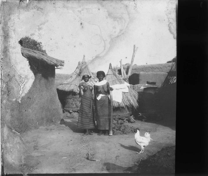 Femmes posant devant des huttes