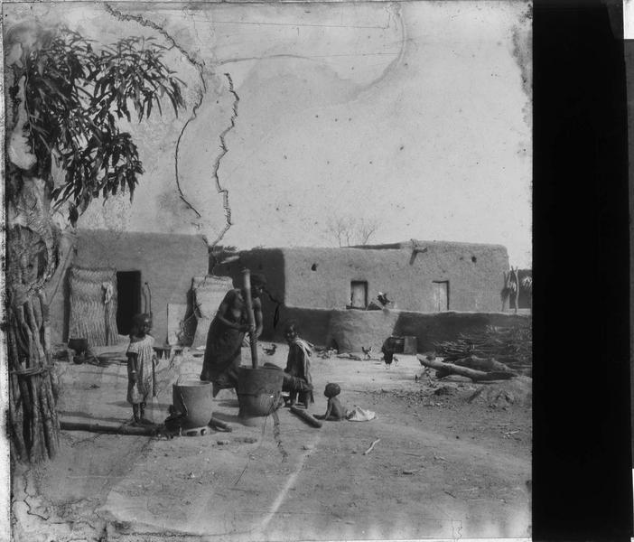 Femme pilant le grain entourée d'un homme et d'enfants dans une cour