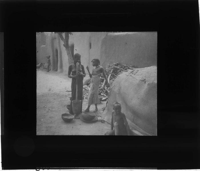 Femmes pilant le grain et enfants