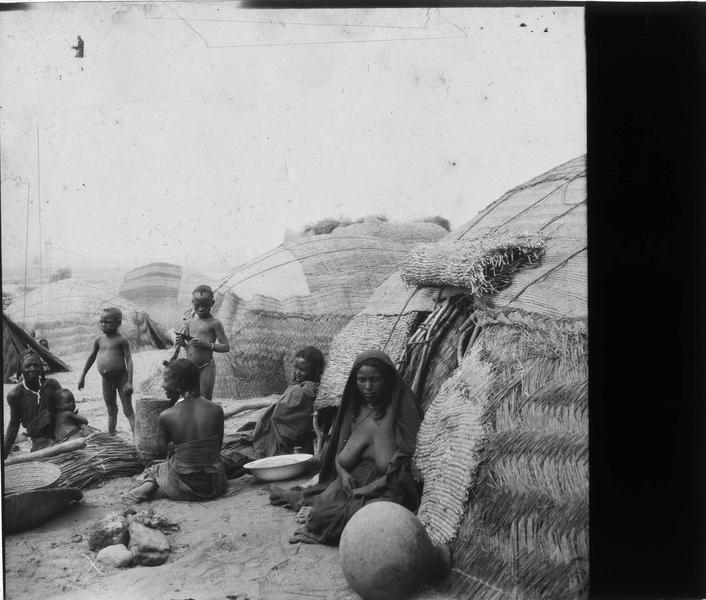 Femmes et enfants devant des huttes