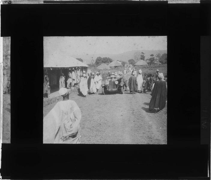 Arrivée d'une voiture de touristes en tenue coloniale dans un village