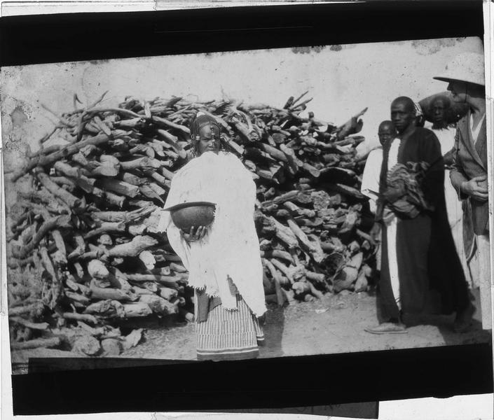 Femme avec un récipient dans la main posant devant un stock de bois