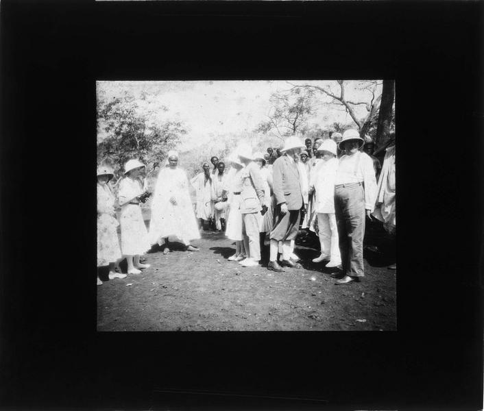 Touristes en tenue coloniale et chef d'un village
