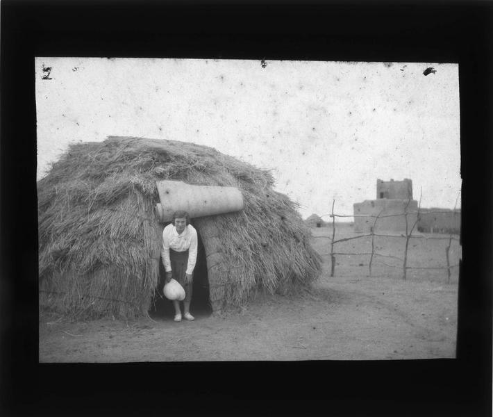 Femme en tenue coloniale sortant d'une hutte