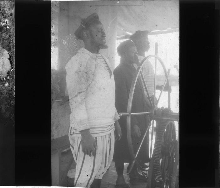 Capitaine et deux marins à la barre du bateau à vapeur 'Mage' sur le fleuve Niger