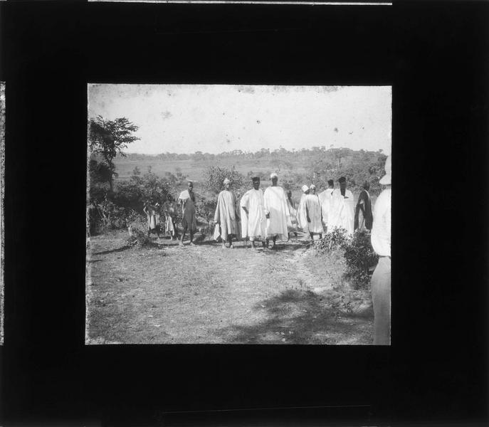 Groupe d'autochtones et chef de village sur un chemin