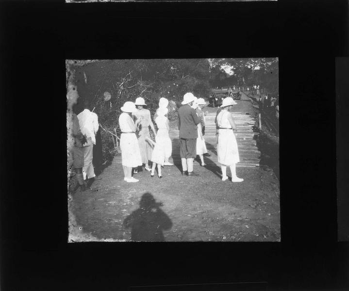 Groupe en tenue coloniale devant un pont en bois et voitures en arrière-plan