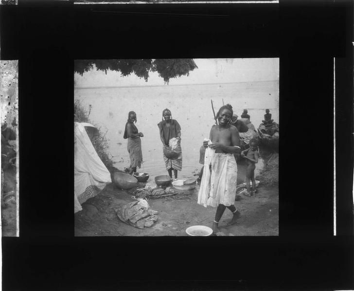 Femmes lavant du linge au bord du fleuve Niger, enfant et piroguiers