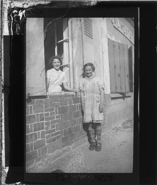 Portrait de deux femmes à la fenêtre d'une maison