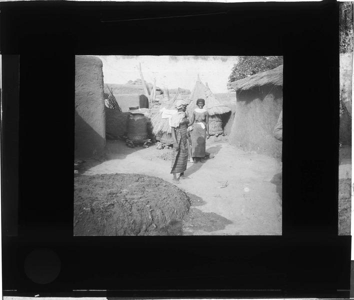 Deux femmes au milieu de huttes