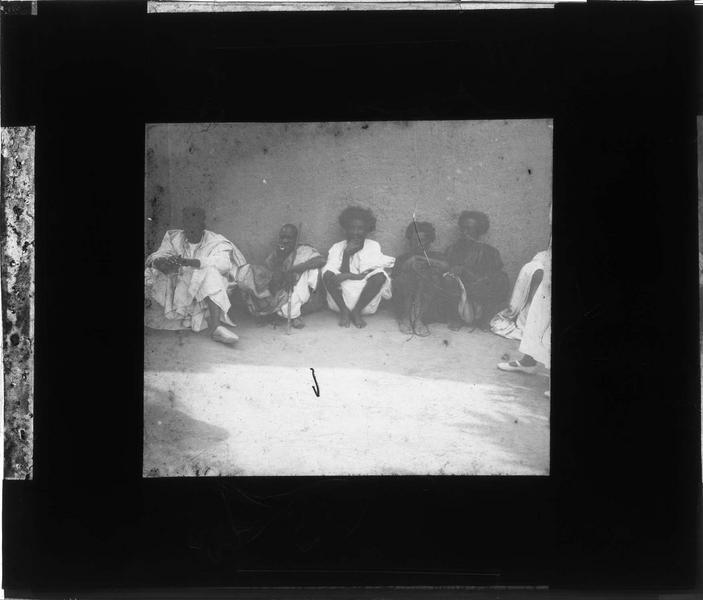 Hommes assis le long d'un mur de la mosquée