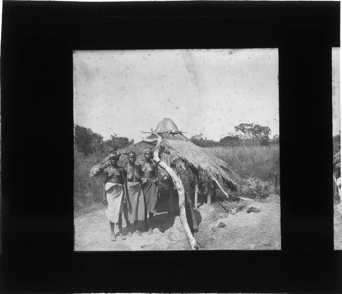 Trois femmes devant une hutte