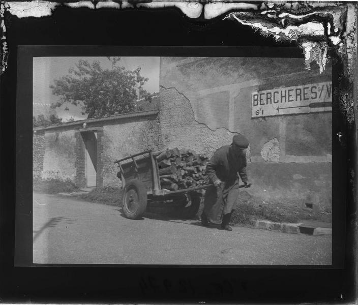 Homme tirant une charrette remplie de bois à l'entrée du village