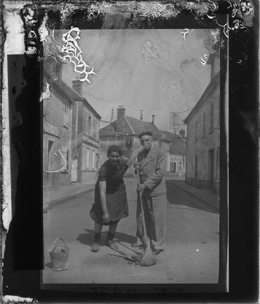 Portrait d'un homme et d'une femme au milieu de la rue avec balai et seau