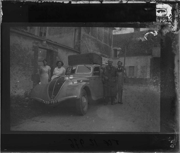 Portrait de groupe devant une maison et voiture Peugeot 402
