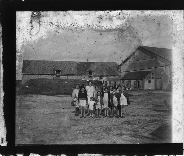 Portrait de groupe : une femme et des fillettes dans une cour de ferme