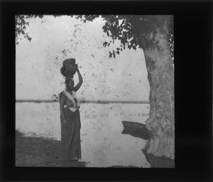 Femme portant une cruche sur la tête au bord du fleuve Niger