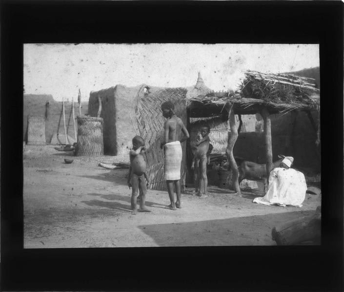 Enfants devant un abri avec une chèvre