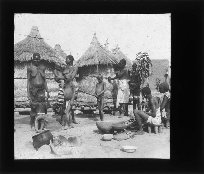 Femmes et enfants au milieu des huttes