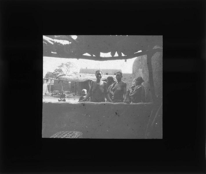 Femmes et enfants depuis l'intérieur d'une hutte