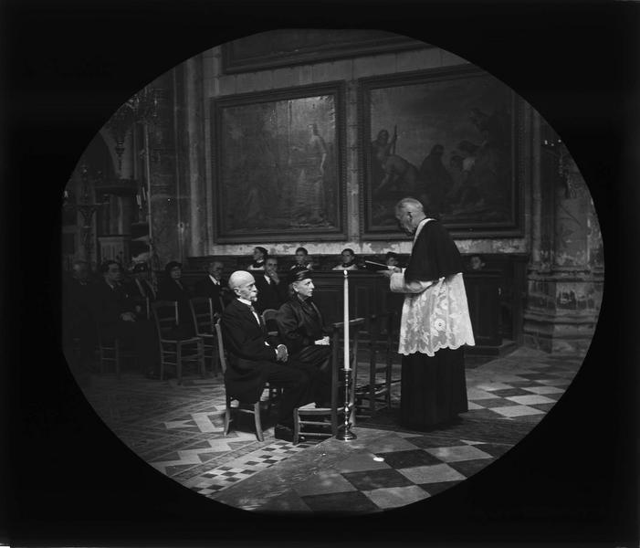 Intérieur : célébration d'un anniversaire de mariage (noces d'or), couple assis face à un prêtre