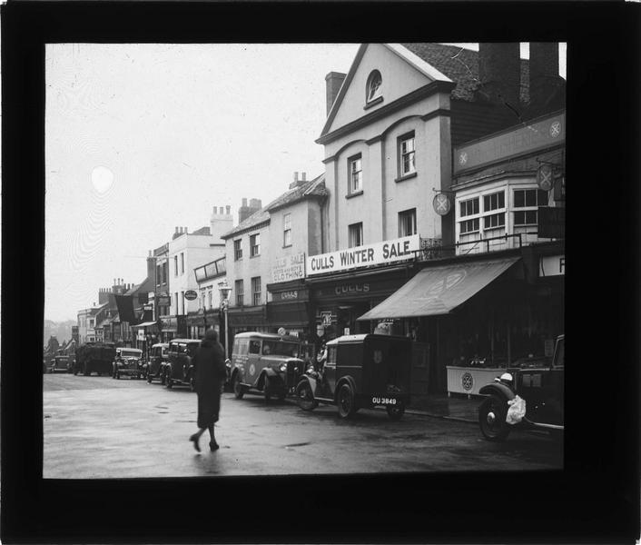 Façades sur rue commerçante avec automobiles et femme traversant