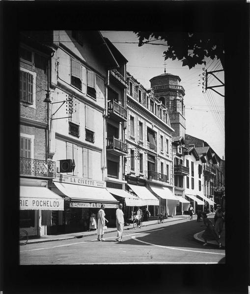 Façades sur rue animée et clocher de l'église Saint-Jean-Baptiste en arrière-plan