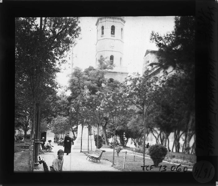Statue depuis le square animé et clocher de la cathédrale en arrière-plan