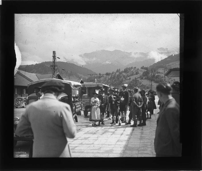 Groupe en costumes traditionnels dans la rue, voitures et montagne en arrière-plan