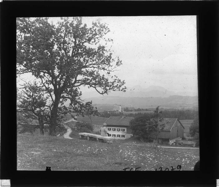 Panorama avec Alpes en arrière-plan et femme assise sur un banc