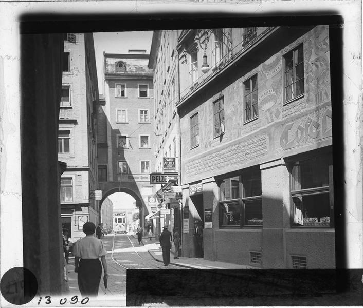 Façades sur rue animée avec passage voûté et tramway