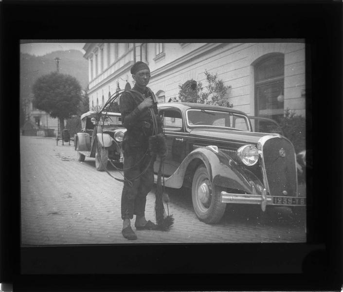 Portrait d'un ramoneur devant la façade d'un hôtel avec voitures en stationnement