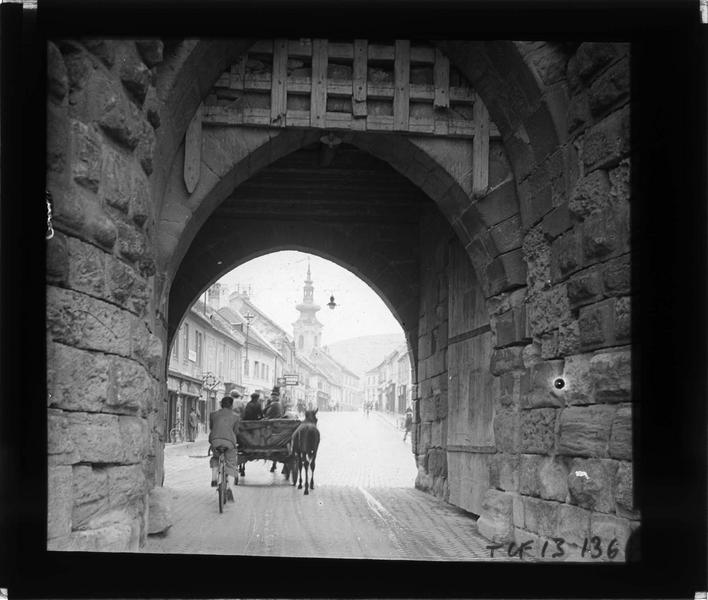 Passage sur rue animée avec cycliste, calèches et clocher en arrière-plan