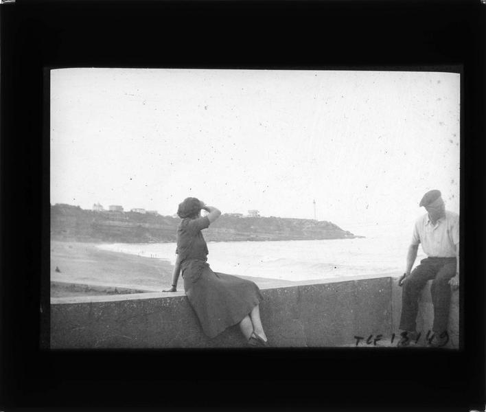 Plage avec phare de Biarritz en arrière-plan, vue animée avec femme et homme assis sur une avancée