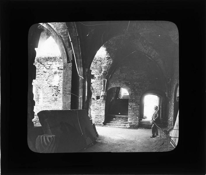 Cloître, intérieur : galerie et escalier menant aux dortoirs en ruines avec homme