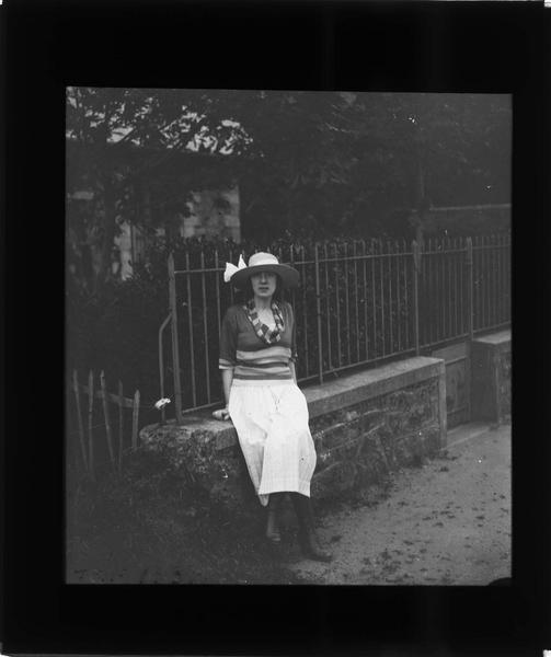 Portrait d'une femme (Gabrielle) posant devant la grille d'une maison