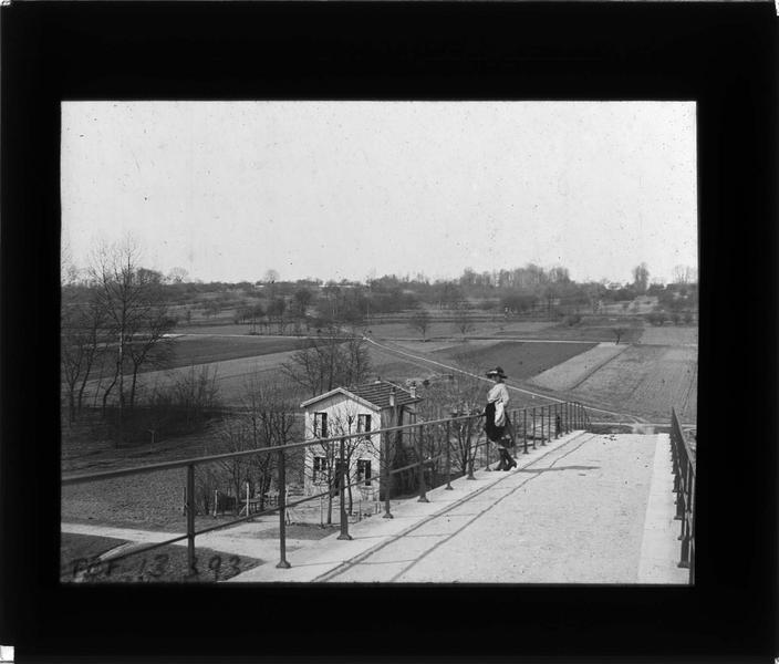 Champ et maison depuis le pont et femme posant
