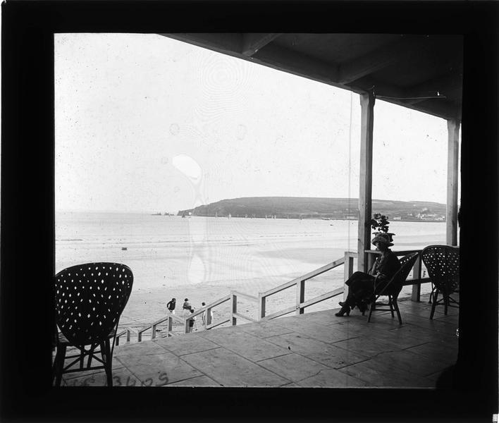 Terrasse couverte donnant sur la plage et la pointe de Gador, et femme (Gabrielle) assise