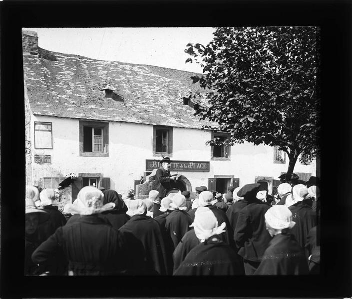 Crieur publique parlant à la foule devant la 'Buvette de la place'
