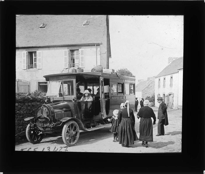 Façades sur rue animée et voiture des Postes et Télégraphes avec voyageurs