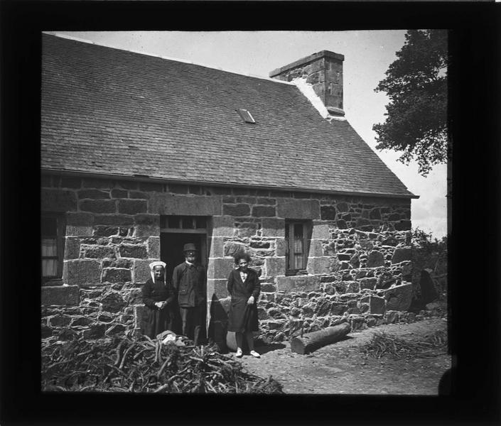 Façade et famille (Evenou) posant devant la porte d'entrée