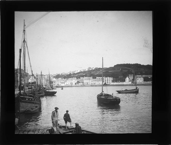Ensemble avec bateaux et marins et maisons en arrière-plan